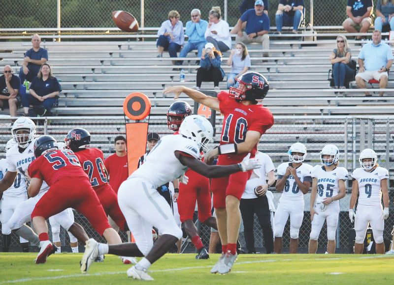 Southern Nash quarterback Brock Alford (10) gets off a throw under pressure during a Sept. 3 win over visitor C.B. Aycock. Alford threw his first two touchdown passes on Friday, both to senior Jackson Vick, during the Firebirds' 42-14 road victory over Bunn.