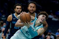 Charlotte Hornets guard LaMelo Ball works around Memphis Grizzlies forward Kyle Anderson during the second half of a preseason NBA game Oct. 7 in Charlotte.
