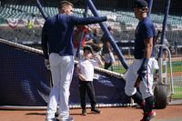 Atlanta Braves' Freddie Freeman, left, works out with his child Charlie Freeman, center, during a Friday workout ahead of baseballs National League Championship Series against the Los Angeles Dodgers in Atlanta.