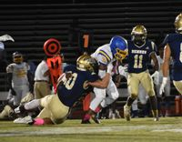 Fike's Noah Rowland (10) and Nigle Richardson, hidden, bring down an East Wake ball carrier during the first half of Friday's game at Fike. The Golden Demons won 41-13.