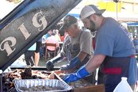Jon Jefferys, front, and Ron Sullivan cook barbecue for St. Mary Church during Saturday's Pig at the Depot cook-off in Spring Hope.