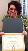 Brittany Ellis holds the certificate she received for completing Peer Mentor training.