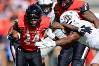 Cincinnati running back Jerome Ford (24) carries the ball as he breaks a tackle against UCF linebacker Jeremiah Jean-Baptiste, right, during the first half of a game Saturday in Cincinnati.