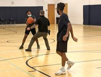 Lt. Felix Killette guards Daebrian Harris while Paul Engran watches during a recent pickup basketball game during open gym at the Zebulon Community Center.