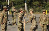 375th Quartermaster Company commander Capt. Elizabeth Mamay, center right, hands the company guidon to 1st Sgt. Karen Strauss during a Saturday activation ceremony.