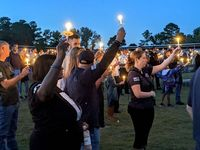 Attendees hold their candles aloft during a Wednesday vigil for Officer Ryan Hayworth of the Knightdale Police Department, who died when a motorist struck his stopped patrol vehicle.