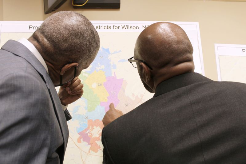 Reginald Speight and Councilman Michael Bell discuss one of Wilson's proposed redistricting maps on Thursday.