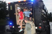 A Wake Forest police officer helps kids out of a vehicle during National Night Out on Monday.