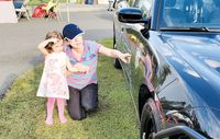 A parent teaches her child the meaning of the Butner Public Safety logo on the side of a patrol car during Tuesday evening's National Night Out event at Butner Athletic Park. BPS and its partners held the annual event to give local residents an opportunity to interact with first responders and law enforcement officers in a positive environment.