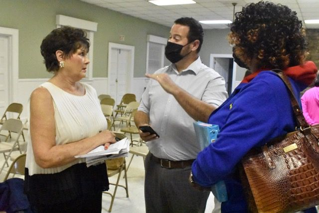 Spring Hope residents Eva Denton, left, and Charlene Battle, right, question mayoral candidate Kyle Pritchard, center, about his driving while impaired conviction and accusations of drugs and domestic violence after Thursday's forum at the Community Building.