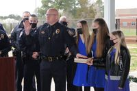 Rolesville's new police chief, David R. Simmons II, is sworn in on a Bible held by his daughters, from left, Bailey, Breanna and Bristol.