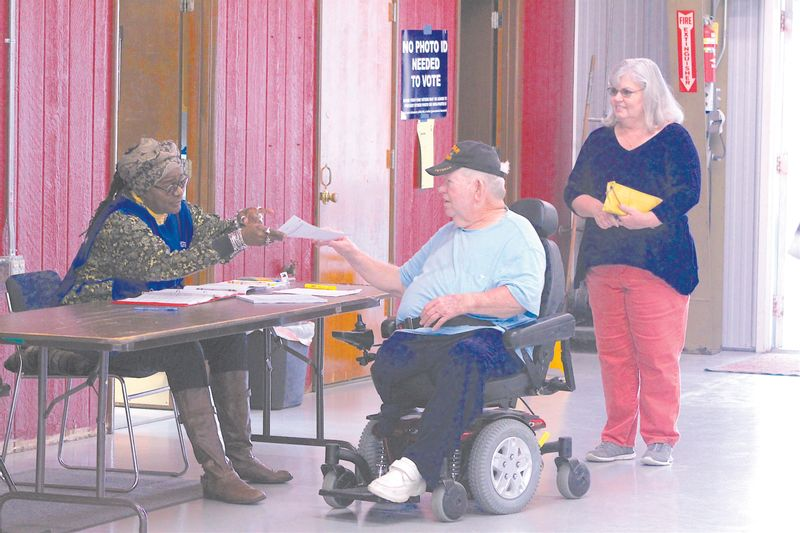 Elections judge Angie Royal hands Van Raper his voting paperwork in Lucama as voter Donna McMurray waits at the Crossroads Volunteer Fire Department on Nov. 7, 2017.