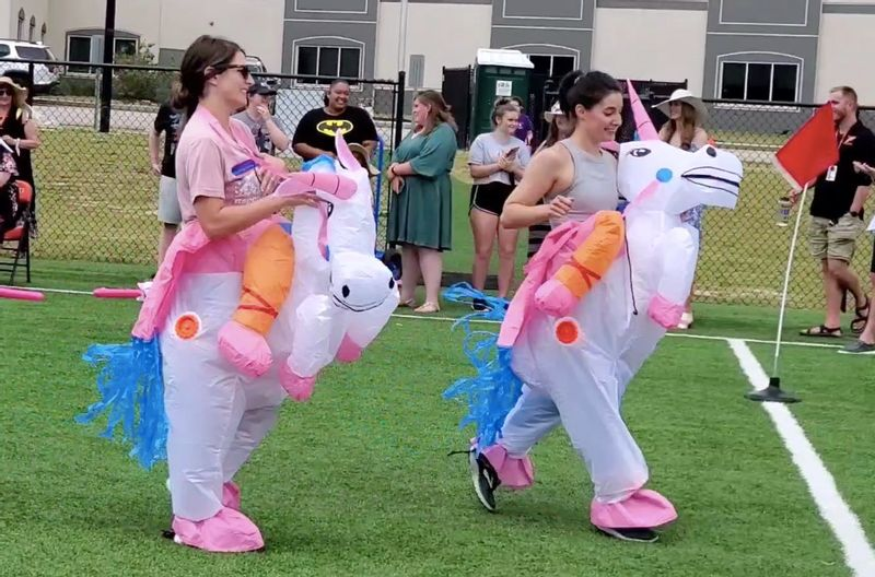 Casey Carey and Rachel Fowler race to the finish line in their inflatable unicorn costumes during Falls Lake Academy's field day last week.