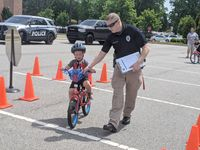 Owen Shook, 4, gets a helping hand from Rolesville Police school resource officer Brian Strickland during the bike rodeo at Thales Academy on Saturday morning.