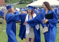 Three friends celebrate the end of the Wake Forest graduation ceremony.