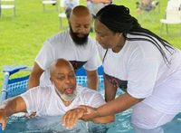 Brother Eddie Junior and Apostle Telley Pender Lucas baptize James Speight during A Heart for God International Ministries' June 12 community baptism at Family Car Wash on Nash Street.
