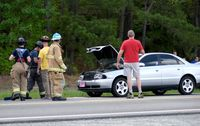 Members of the Creedmoor Volunteer Fire Department remove debris from U.S. Highway 15 and check if fluids are leaking from a car involved in a crash  near Hester Road on June 29.