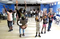 Teachers and students participate in a dance depicting all the animals of Africa during a St. John CDC Save-A-Youth summer camp.
