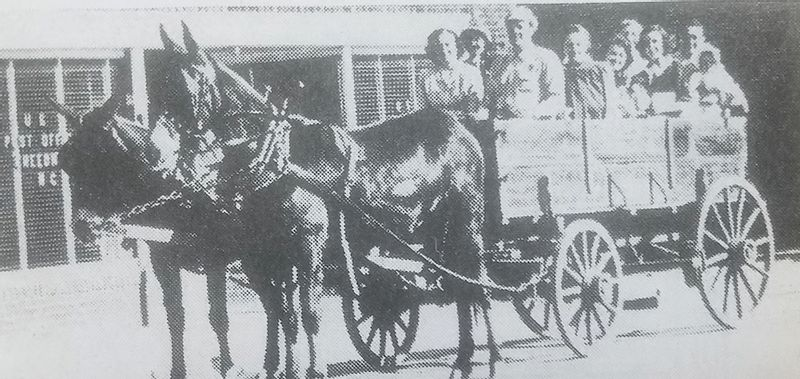 Billy and Mary Lyon and their family take Joe and Helen Davenport and their family on a leisurely Sunday ride down Main Street Creedmoor in a mule-drawn wagon in 1952.