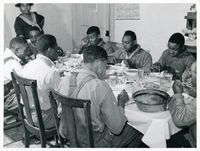 After the white men finished dinner, Black tenants and neighbors in 1939 eat after a day of corn-shucking at Mrs. Fred Wilkins' home in Tally Ho, near Stem.