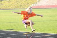 Katie, 9, jumps over one of the hurdles at the Franklin County Runner's Camp held at Franklinton High School. Ma