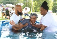 Emani Lucas of Wilson, center, is baptized by Apostle Telley Pender Lucas of A Heart For God International Ministry on Saturday as intercessor Eddie Ellis, left, assists.