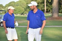 Justin Hayes, left, and Brock Godwin chat after they combined for a birdie on the 15th green Saturday afternoon at Wilson Country Club in the 28th annual Wilson Cup.
