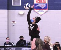 East Wake Academy's Sinead Thomas goes down for a spike on the ball.