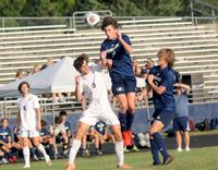 Heritage midfielder Auggie Flaim rises above a Broughton player to get his head on the ball.