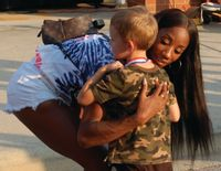 Keni Harrison hugs a little boy before an awards ceremony in her honor at Clayton High School, her alma mater.