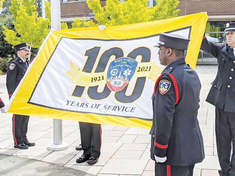 The honor guard prepares to raise the 100th anniversary flag Wednesday at Town Hall. It will fly until Aug. 3, 2022.