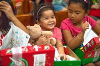 Children open their Operation Christmas Child gifts during a distribution at Cornerstone Christian Church in Saipan. Since 1993, Samaritan's Purse has collected and delivered more than 186 million gift-filled shoeboxes to children in more than 160 countries and territories.