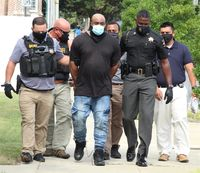 Wilson County Sheriff Calvin Woodard, front right, and deputies walk Adrian Tynrell Horne to the sheriff's office on Wednesday afternoon. Horne is charged with two counts of first-degree murder.