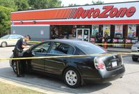 Wilson police look for evidence around a Nissan Altima in the AutoZone parking lot Saturday afternoon on Tarboro Street.