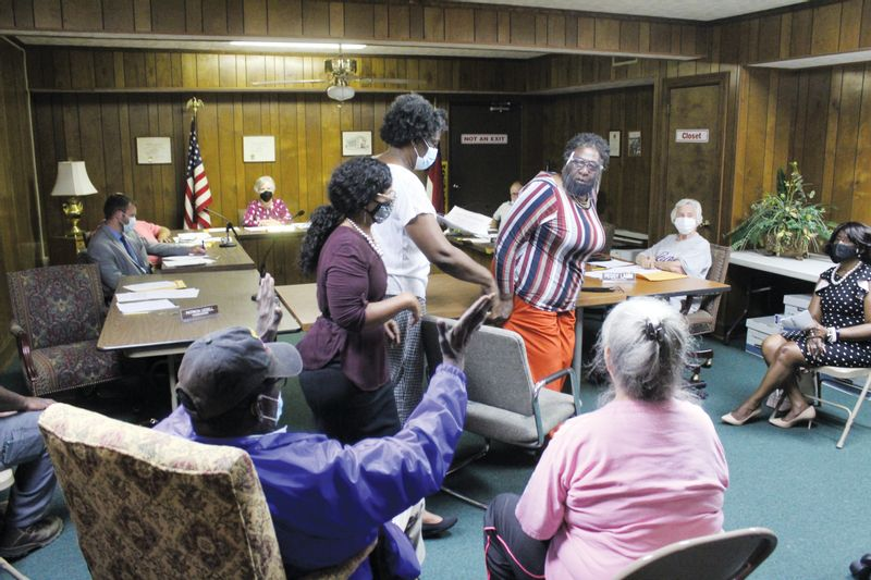 Lucama resident Gladys Martinez, standing at right, is led away by her daughter and Commissioner Patricia Uzzell during the Lucama Board of Commissioners' Monday meeting.