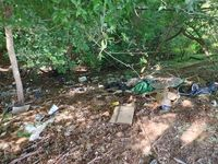 Trash litters a homeless camp in Raleigh.