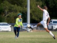 Carrboro's Phillip Klem, right, sends a flying kick right at Jason Carroll, keeper for the Vikings, during Wednesday's contest.
