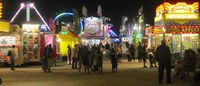 Visitors enjoy a Tuesday stroll around the midway as night falls on the Wilson County Fair.