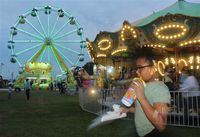 Eleven-year-old Mariyah Perez of Wilson enjoys a beverage as she explores the Wilson County Fair at dusk Tuesday.