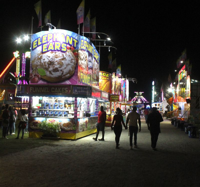 As night falls on the Wilson County Fair, visitors enjoy a Tuesday stroll around the midway.