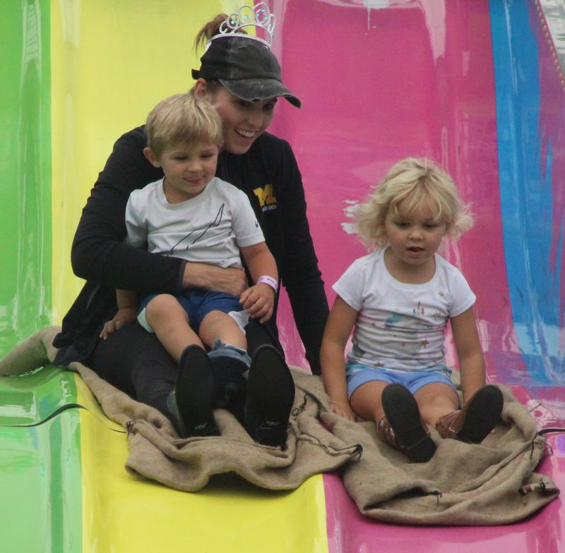 Chellsie Chrysanthou of Wilson slides down the Fun Slide with son Elliott, 2, and daughter Iris, 4, on Tuesday at the Wilson County Fair.