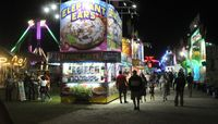 As night falls on the Wilson County Fair, visitors enjoy a stroll around the midway.