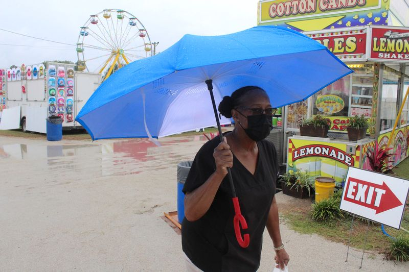 Cleora Ward of Stantonsburg leaves the Wilson County Fair in the rain Wednesday.