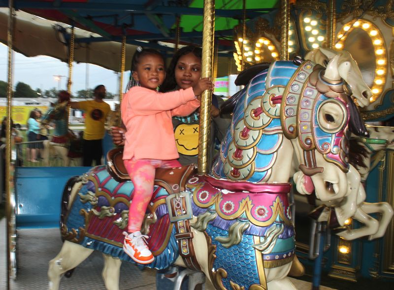 Kinsley Perry and mother Precious Perry of Wilson ride the Wilson County Fair merry-go-round on Tuesday.
