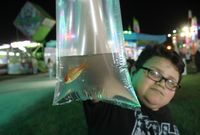 Christian Brown of Stantonsburg shows off the goldfish he won Tuesday at the Wilson County Fair.