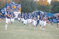 The Smithfield-Selma High School Spartans run onto the playing field before the start of Friday's homecoming game.