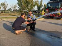 Sixteen-month-old Bryson learned how to use a fire hose under the supervision of Nathen Fosness, left, and firefighter Mitchell Medlin.